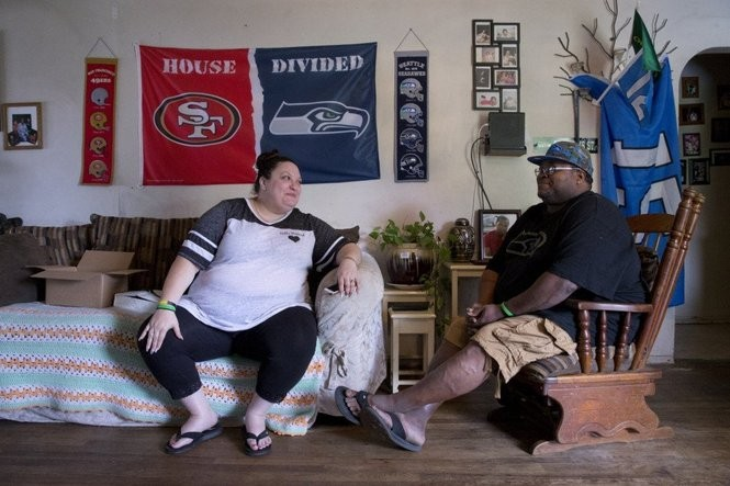 Natasha, left, watches football on a recent Sunday with her husband, Larnell Sr. Their son was killed in Gresham in August. Beth Nakamura/The Oregonian/OregonLive