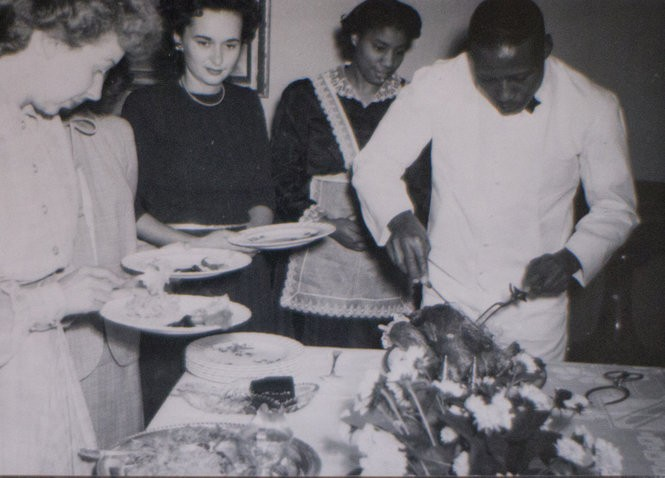 Thelma Glover, shown here (third from left) in the outfit she wore as a domestic, watches as her husband, Cephas, carved the holiday turkey for a Lake Oswego family.
