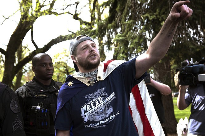 FILE--In this April 29, 2017, file photo provided by John Rudoff, Jeremy Joseph Christian, right, is seen during a Patriot Prayer organized by a pro-Trump group in Portland, Ore. Christian, the man accused of stabbing two commuters to death who tried to stop him from hurling anti-Muslim insults at young women on a light-rail train came from a stable family and was a rambunctious teenager who spiraled out of control as he entered his teenage years, according to court records and acquaintances.