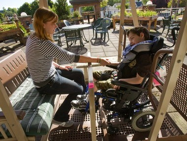 Amy Tennant holds the hand of Joel Petz, who suffers from seizures and was diagnosed with cerebral palsy, as the two swing on a glider at Providence Medical Center's Child Center in Northeast Portland. Petz and many other students at the center find themselves in limbo after Portland Public Schools abruptly informed parents that they are not legally responsible for their education.