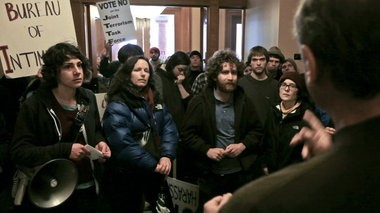 """Protesters stormed into Portland City Hall in 2011 to deliver petitions but the group couldn't get beyond a lobby security point. The protesters began shouting """"City Council Come on Down!"""" Only Commissioner Randy Leonard (right) appeared."""