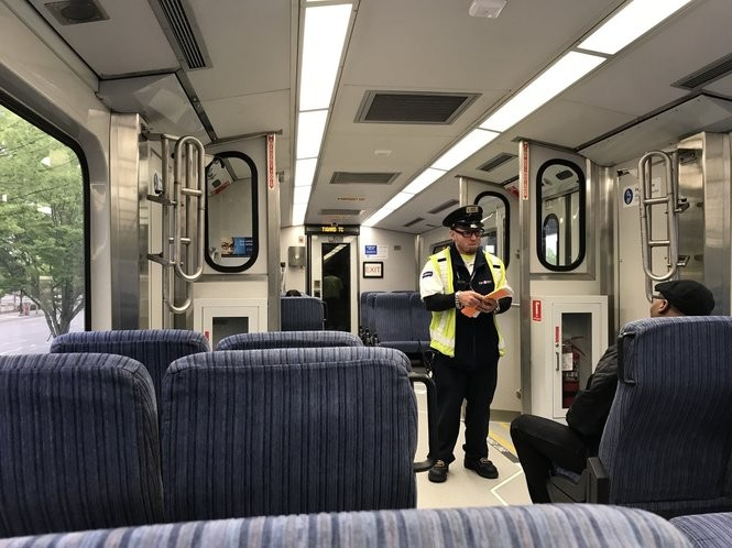 Lucky Mincer (seated) chats with a conductor performing fareinspections on the WES train in May, 2018. Mincer said he loves the sense of community on the commuter rail line.