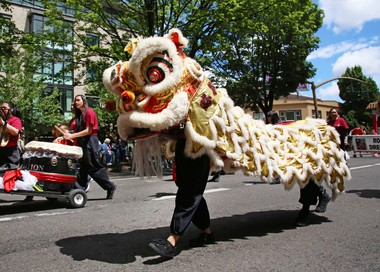 Lion dancers with Chinese Community of Greater Portland Dragon Team make their way down West Burnside Street during the 2018 Grand Floral Parade.