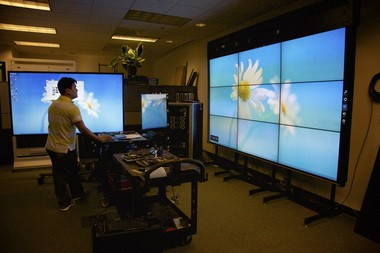 Planar testing engineer Brandon Mach working on a pair of large displays in the company's Hillsboro research lab. The company has narrowed its focus to concentrate on large, interactive displays favored by marketers and retailers.