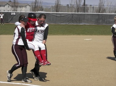 Central Washington softball players Liz Wallace (left) and Mallory Holtman carry Western Oregon's Sara Tucholsky around the bases after she blew out her knee after hitting a home run Saturday, April 26, 2008, in Ellensburg, Wash.