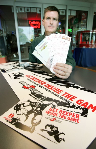 Oregon Lottery public affairs representative Chuck Bauman displays lottery Sports Action entry forms and promotional material in 2005, after lawmakers introduced a bill to end the sports betting games in the state.