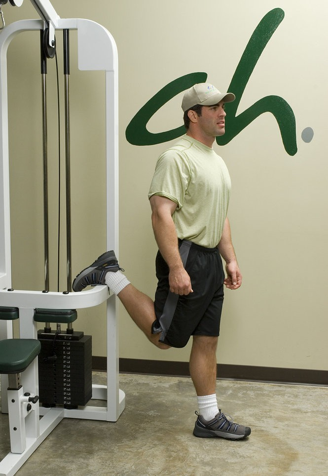 Standing quadriceps stretch. Note position of the foot to reduce strain on ankle ligaments and position of the knee, which is slightly behind the supporting knee in order to optimally stretch the quadriceps. The low back should not be arched. Photograph courtesy of Ty Downing / 503.653.3887