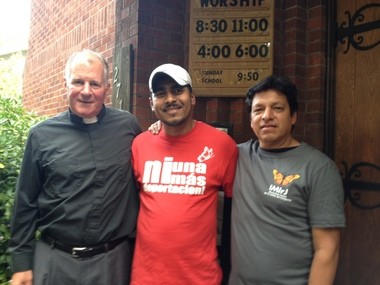 Pastor Mark Knutson at the door of Augustana Lutheran, with labor activist Francisco Aguirre, and Marco Mejia with the Interfaith Movement for Immigrant Justice