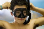 Koji Wieber, a Grant High School junior, pulls on his snorkel mask before diving into the pool at Osborn Aquatic Center. Underwater hockey, which started decades ago in England, is slowly making its way across the country.