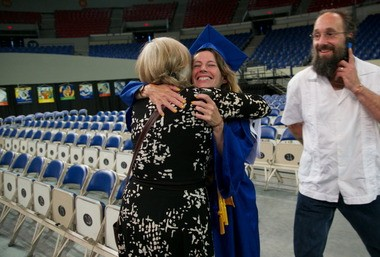Michelle Reers, PCC's student speaker this year, hugs her first academic advisor at PCC Marta Hoenig before the PCC graduation ceremony at Memorial Coliseum. On the right is her husband Cen Reers, who is also pursuing a PCC degree.
