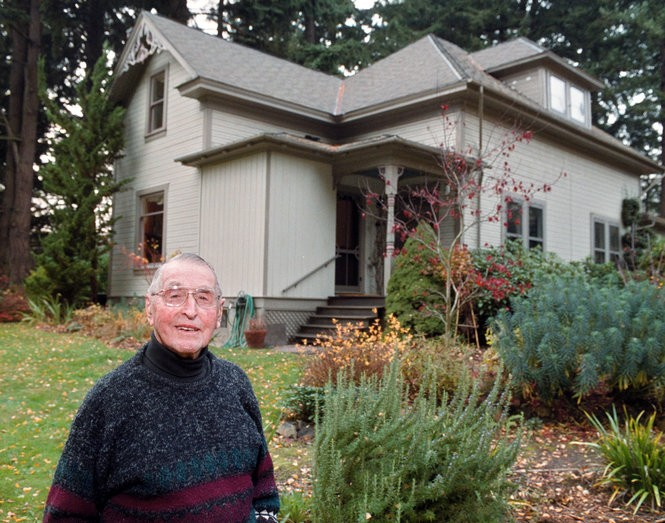 In this 2002 file photo, Curtis Tigard, 93, stands in front of the home where he grew up.