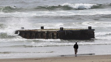 In this June 6 photo, a man looks at the tsunami dock that washed ashore on Agate Beach in Newport.
