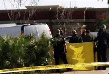 Arizona officials check a body found in bushes by a landscaper in the Phoenix suburb of Mesa on Thursday. A body matching Arthur Harmon's description was found with an apparent self-inflicted gunshot wound, spokesman Sgt. Steve Martos said. Harmon is a suspect in a shooting that killed a man and critically wounded another.