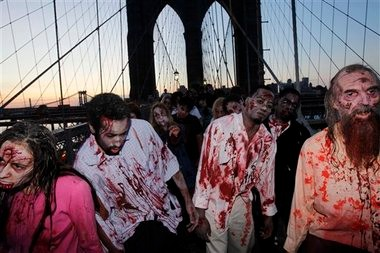 """Costumed actors, promoting the Halloween premiere of the AMC television series """"The Walking Dead"""", shamble along the Brooklyn Bridge while posing for pictures in New York, in October 2010. Clemson University English professor Sarah Lauro says people are more interested in zombies when they're dissatisfied with society as a whole."""