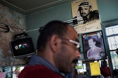 U.S. President Barack Obama appears on television, left, at a restaurant next pictures of late Palestinian leader Yasser Arafat, top, and late Iraqi President Saddam Hussein, bottom, in the West Bank city of Ramallah, Thursday, March 21, 2013. Obama's visit to the West Bank was largely met by indifference. Obama on Thursday urged Israelis and Palestinians to get back to peace talks but offered no new ideas on how they might do so, essentially abandoning his previous support of the Palestinian demand for Israel to halt settlement activity before negotiations resume. (AP Photo/Bernat Armangue)