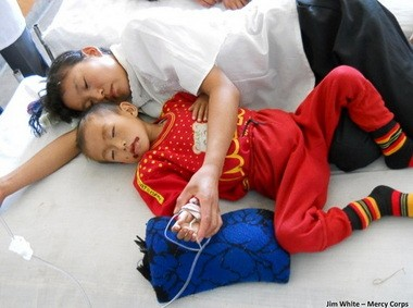A North Korean mother lies with her acutely malnourished son, plagued by sores, at a county hospital in September 2011. Portland-based Mercy Corps and other humanitarian organizations warned of widespread hunger, but the U.S. canceled food aid after North Korea launched a rocket.