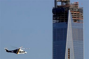 A New Jersey State Police helicopter flies by the construction site of One World Trade Center in Manhattan seen from The Heights neighborhood of Jersey City, N.J., on Monday. New York is securing its city in the wake of explosions near the finish line at the Boston Marathon.