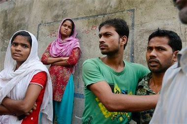 Workers stand outside an 11-story building that houses the Tung Hai Sweater Ltd. factory and apartments after a fire in Dhaka, Bangladesh. The fire broke out in the building Wednesday night, not long after the workers of the factory went home for the day.