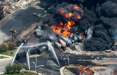 Smoke rises from railway cars that were carrying crude oil after derailing in downtown Lac-Mégantic, Quebec on July 6, 2013. The accident killed 47 people and focused attention on the growth of trains hauling crude oil from North Dakota.