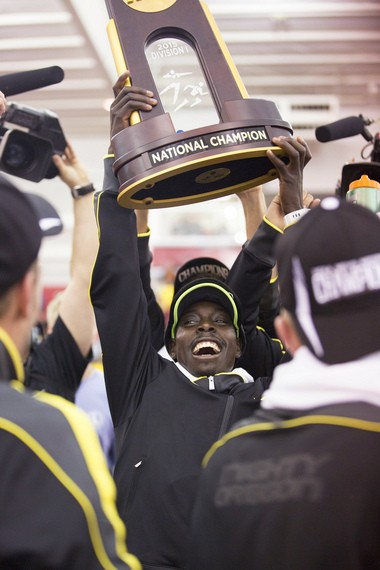 Edward Cheserek hoists Oregon's championship trophy during the Ducks' victory celebration.