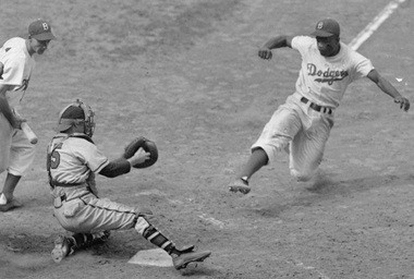 This Aug. 22, 1948 file photo shows Brooklyn Dodgers Jackie Robinson, right, stealing home plate as Boston Braves' catcher Bill Salkeld is thrown off-balance on the throw to the plate during the fifth inning at Ebbets Field in New York.