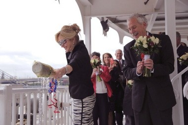 Claudette Waggoner does the honors as husband John Waggoner, CEO of the American Queen Steamboat Co., looks on during the naming ceremony Saturday of the American Empress riverboat at the downtown Portland seawall.