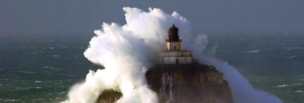 A wave crashes over the Tillamook Rock Lighthouse off the Oregon coast.