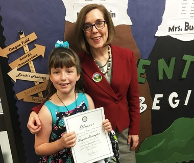 Gov. Kate Brown poses with Brigette Harrington, a fourth grader whose essay won her a spot in the 2018 Capitol Christmas tree lighting.