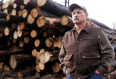 Mark Bagett, a Canyon Creek homeowner whose 240 acres of timbered land was completely burned over, stands in front of a pile of salvage that will be useful only as firewood.