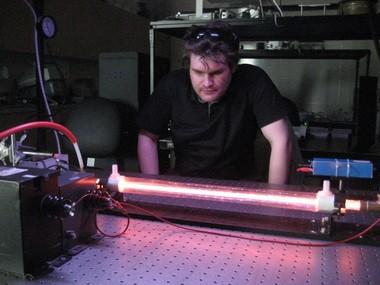 Peter Dekluyver, 26, tests his CO2 plasma tube at Oregon Tech's optoelectronics lab