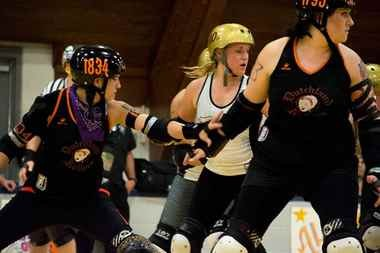 The Rollers set up a wall to block the opponent's jammer from scoring.