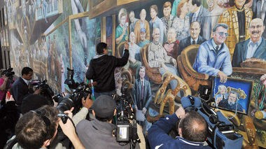 """Artist Michael Pilato paints over the image of Jerry Sandusky in his mural """"Inspiration"""" in """"Happy Valley."""" (Courtesy of Music Box Films)"""
