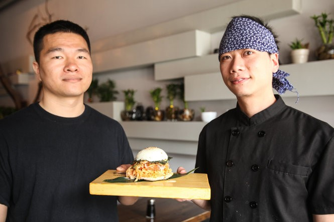 Bubblefish co-owners Xu Lin (left) and Edison Wang (right) with the restaurant's sushi burger. Bubblefish is located at 909 Arch St. in Philadelphia's Chinatown. JULIA HATMAKER | jhatmaker@pennlive.com
