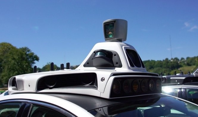 This detail image shows the top-mounted lidar system, which rotates for a 360-degree scan, above the traffic light camera and another camera array on one of Uber's self-driving Ford Fusions.