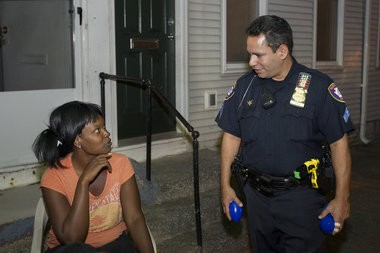 Harrisburg police officer Gabriel Olivera talks with Tia Williams of Harrisburg during a walking street patrol last year.