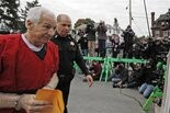 Former Penn State University assistant football coach Jerry Sandusky, left, is escorted by a police officer past photographers as he arrives for sentencing at the Centre County Courthouse in Bellefonte, Pa., Tuesday, Oct. 9, 2012. (AP Photo/Gene J. Puskar)
