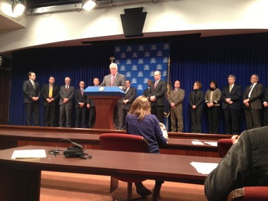 Gov. Tom Corbett announces he will not propose cutting funding for the state's public higher education institutions, which is a first for his administration. Lawmakers and university leaders stand behind him and Education Secretary Ron Tomalis to his right.