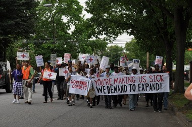"""Medicaid expansion supporters march to the governor's residence Wednesday to stage a """"sick-in."""""""