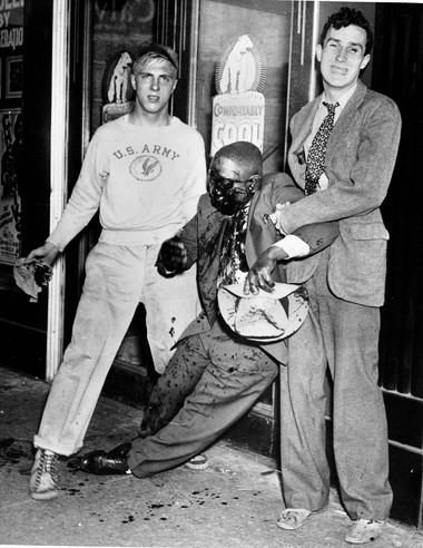 FILE - In this June 21, 1943 file photo, two white youths help a black man to his feet after he was badly beaten in street fighting during race riots in Detroit. (AP Photo)
