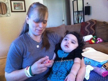 Angel Custer holds granddaughter Jaylah, 18 months, who suffers from the rare degenerative disease Krabbe, which attacks her neurgological system.