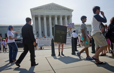 A demonstrator dressed as the 'Bible' stands outside the Supreme Court in Washington on Monday, awaiting the court's decision on the Hobby Lobby case. The Supreme Court says corporations can hold religious objections that allow them to opt out of the new health law requirement that they cover contraceptives for women.(AP Photo/Pablo Martinez Monsivais)