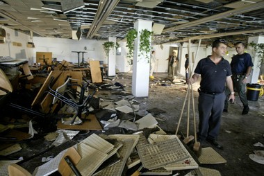 Workers clean the inside of a cafeteria hours after an explosion at Hebrew University in Jerusalem Wednesday, July 31, 2002. A bomb exploded Wednesday in the crowded cafeteria frequented by Jewish, Arab and foreign students, killing at least seven people and wounding more than 70. (AP Photo/David Guttenfelder)