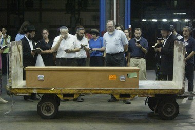 Loved ones of Benjamin Thomas Blutstein, who was killed in a bombing at the Hebrew University in Jerusalem Wednesday, say goodbye over his coffin at the cargo terminal of Ben Gurion airport in Tel Aviv before being shipped to the United States Thursday, Aug. 1, 2002. (AP Photo/David Guttenfelder)