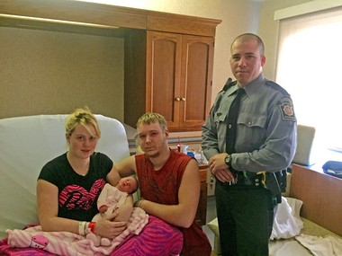 State police Trooper Mark Fisher checks on the mother and infant Wednesday morning at Holy Spirit Hospital in East Pennsboro Township. On Tuesday, Fisher helped deliver the infant in the backseat of the mother's car on state Route 322 west of the Watts exit.