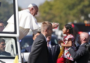 Pope Francis reaches from the popemobile for a child that is brought to him, during a parade in Washington, Wednesday, Sept. 23, 2015. (AP Photo/Alex Brandon, Pool)