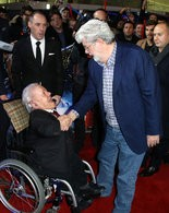 Kenny Baker, left, and George Lucas greet each other at the European premiere of 'Star Wars: The Force Awakens ' in London, Dec. 16, 2015.
