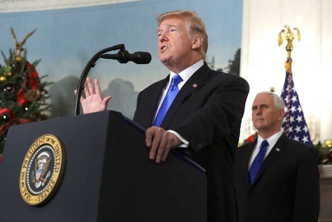 President Donald Trump speaks in the Diplomatic Reception Room of the White House, Wednesday, Dec. 6, 2017, in Washington. Trump recognized Jerusalem as Israel's capital despite intense Arab, Muslim and European opposition to a move that would upend decades of U.S. policy and risk potentially violent protests. Vice President Mike Pence listens at right. (AP Photo/Evan Vucci)