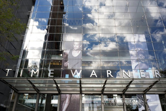 In this Oct. 24, 2016, file photo, clouds are reflected in the glass facade of the Time Warner building in New York. The judge presiding over the government's legal effort to block AT&T's purchase of Time Warner will likely deliver his verdict on Tuesday, June 12, 2018. (AP Photo/Mark Lennihan, File)