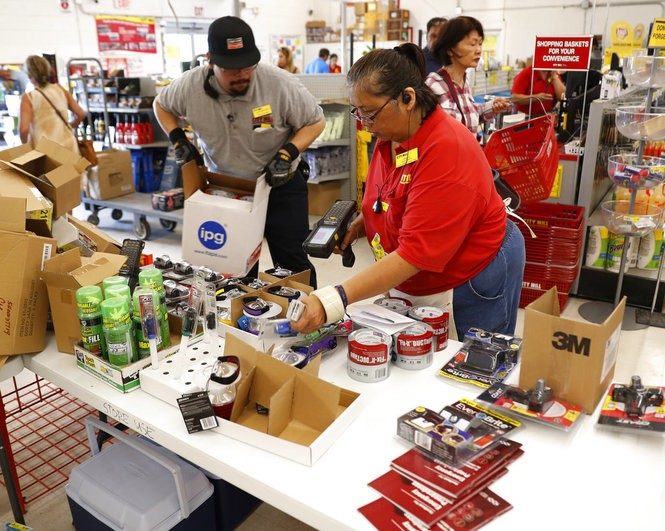 City Mill hardware store sales associates Frank Miller Gascon, left, and Lisa Lavilla fill a table with duck tape, flashlights and other hurricane supplies, Wednesday, Aug. 22, 2018, in Honolulu. Gascon said he's been filling the table up every 10 minutes as supplies are being swept up by shoppers who are preparing for the approaching Hurricane Lane.