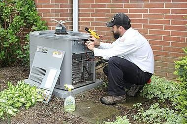 An employee from One Hour Heating and Air Conditioning performs maintenance on a unit.